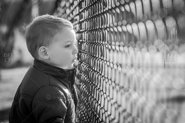 Boy looking through a wire fence