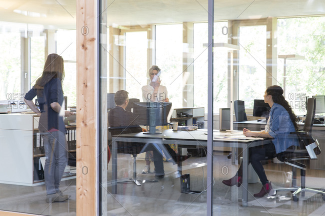 Team of four business people at workplaces in modern office