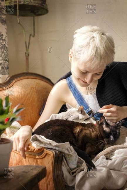 Blonde woman playing with cats