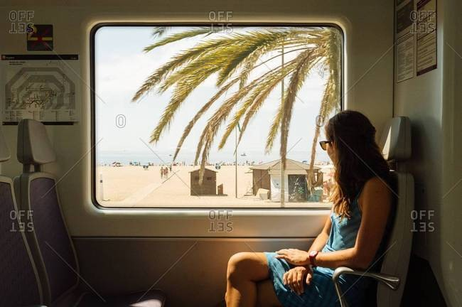 Woman looking through a train window in Spain