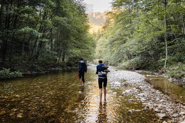 Couple wading in shallow river, near Big Sur, California, USA