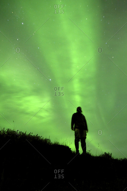 The northern lights ignite the sky as a person look on.