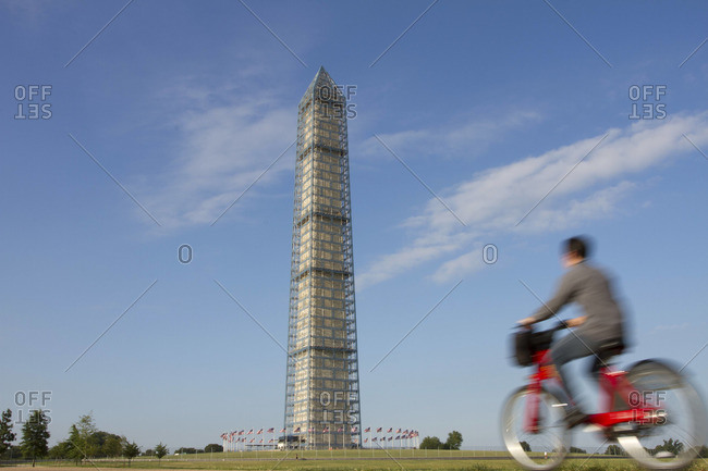 An urban cyclist rides by the Washington Monument.