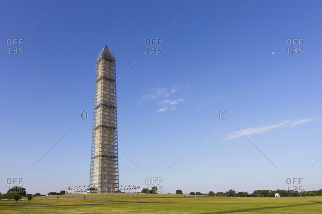 A view of the Washington Monument with the the moon still visible in the morning sky.