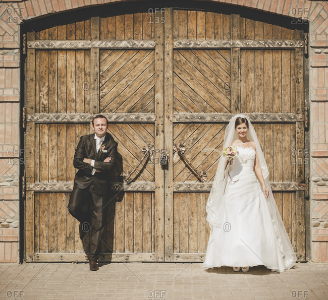 Newlywed couple posing at a wooden entrance
