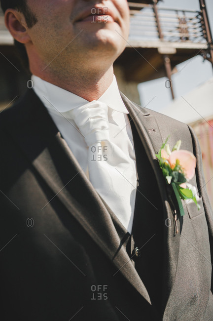 Groom standing in a wedding suit with a boutonniere