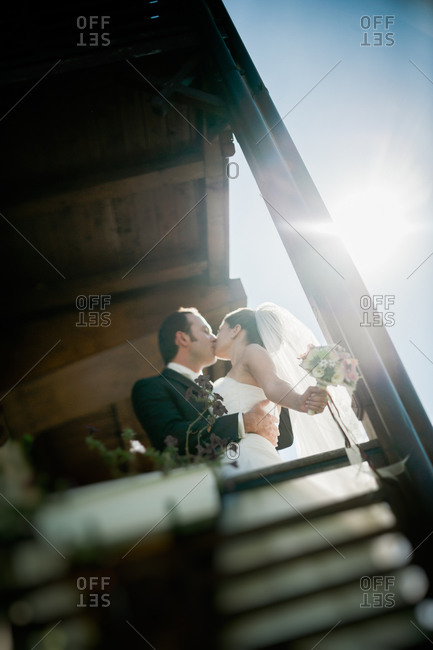 Newlywed couple kissing on a balcony