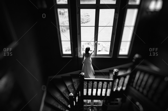 Bride opening a window on a staircase