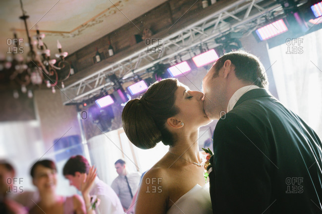 Newlywed couple kissing at their wedding reception