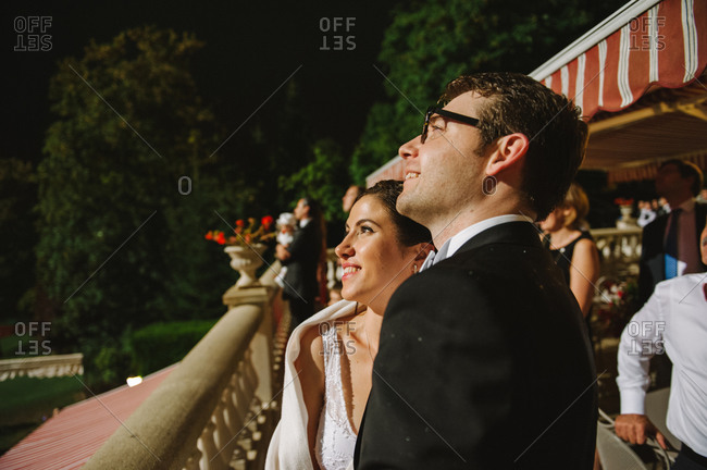 Side view of newlyweds staring fireworks show