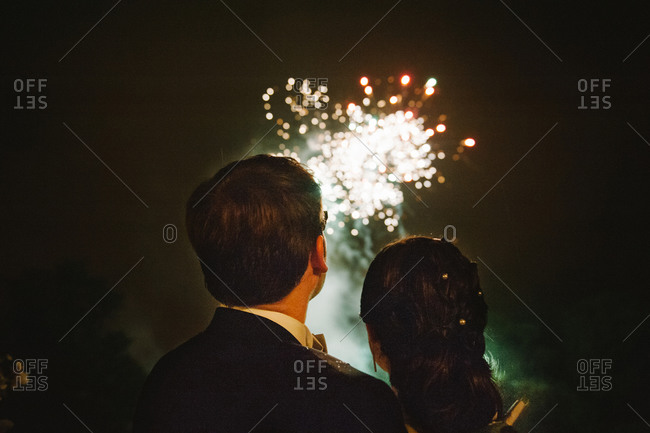 Rear view of newlyweds staring fireworks show