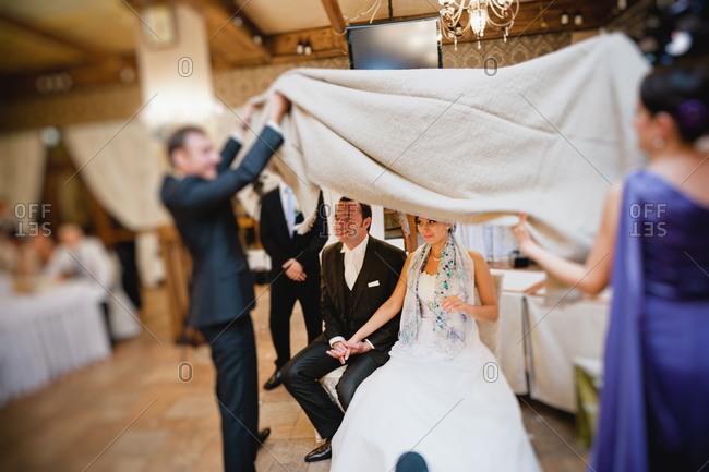 Newlywed couple cover with drape