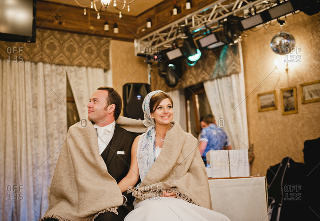 Newlywed couple wrapped with drape