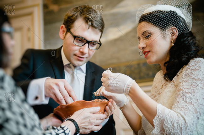 Bride and groom searching their wedding rings in a bowl of grain