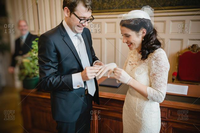 Groom sliding wedding ring on bride's finger