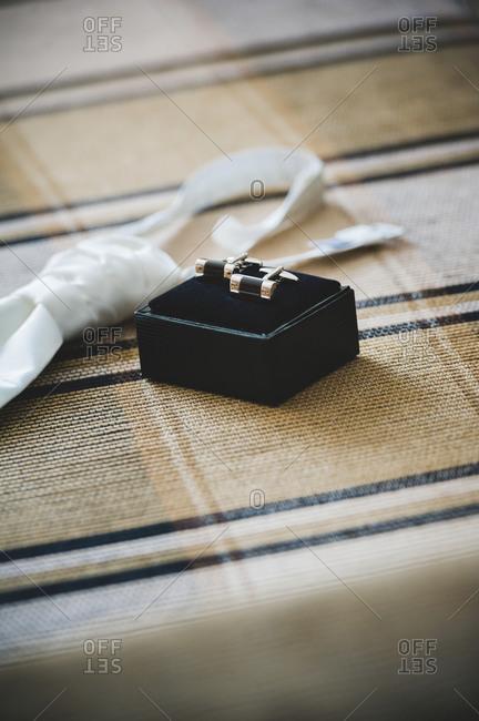 Still life of cufflinks and white silk tie