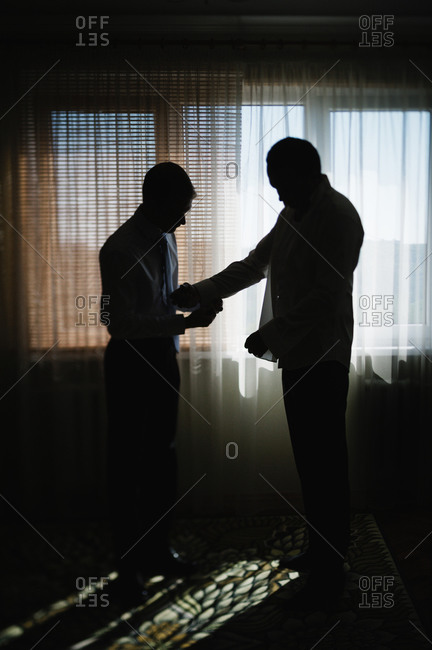 Silhouette of the best man preparing the groom