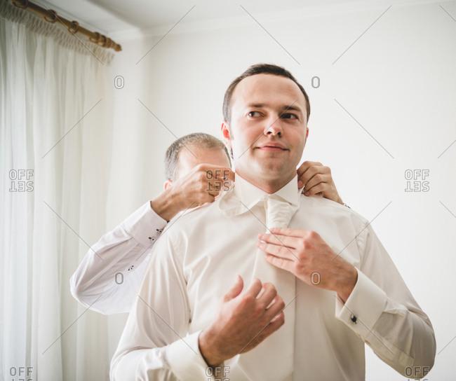 Groomsman fixing the groom's collar