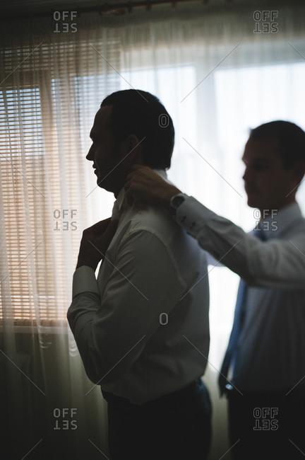 Groomsman adjusting the groom's collar