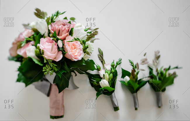 Close up of three boutonnieres and a bridal bouquet