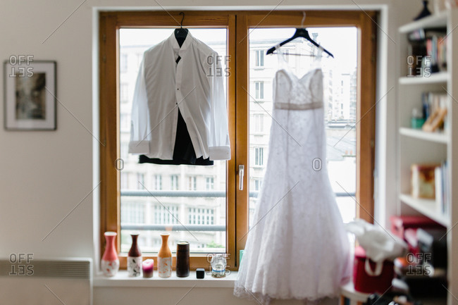 Bride and groom dress hanging by a window