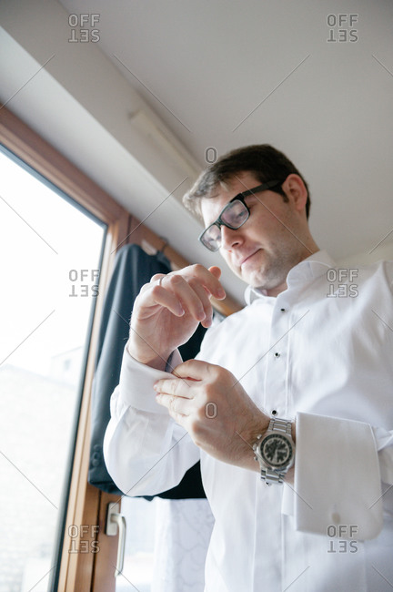 Low angle view of groom putting on cufflinks