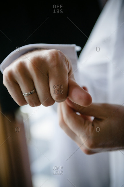 Close up of groom putting on cufflinks