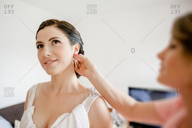 Woman putting earrings on bride