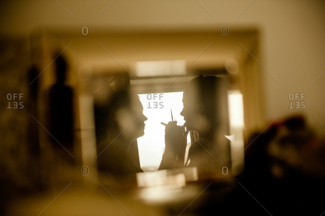 Reflection of woman applying make up on bride