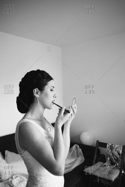 Bride applying lipstick on herself