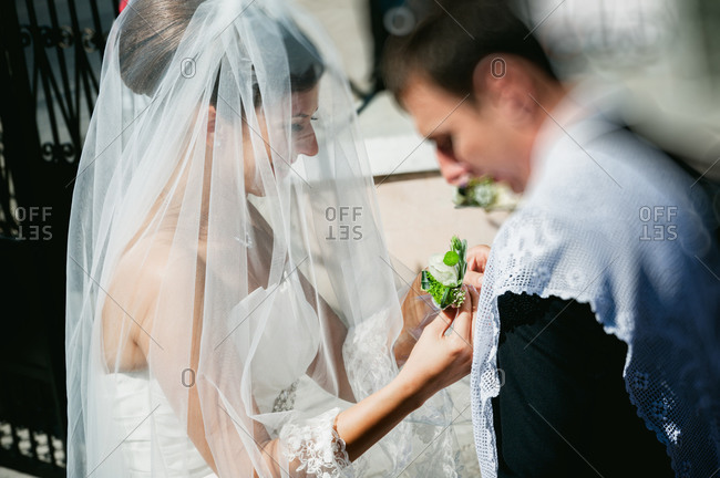 Bride putting a boutonniere on a man