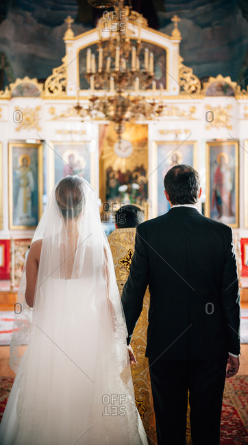 Back view of bride and groom at an Orthodox wedding ceremony
