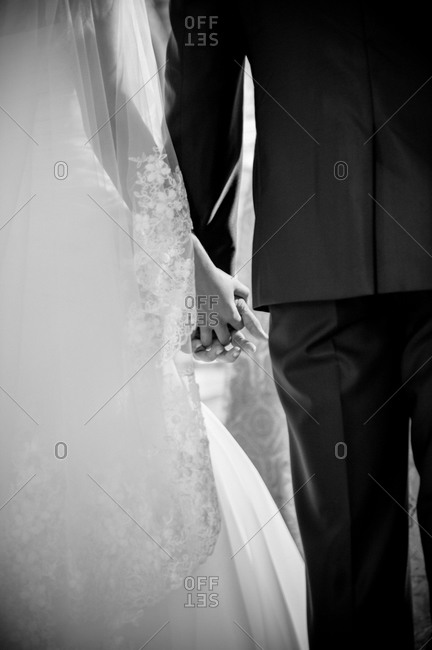 Couple holding hands at their wedding ceremony