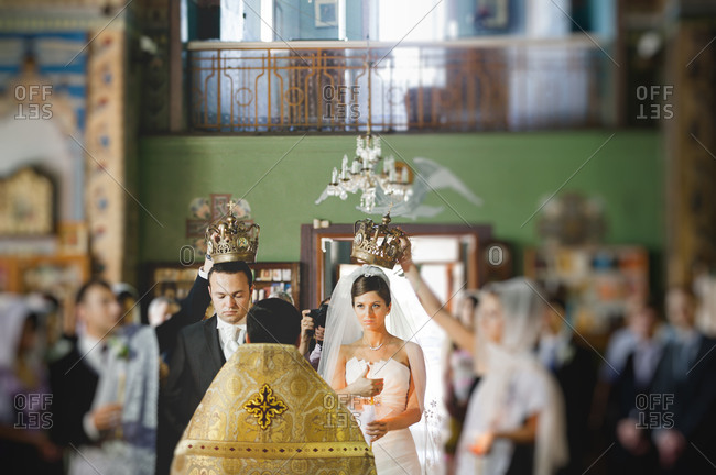 Front view of the crowning of the bride and groom at an Orthodox wedding ceremony