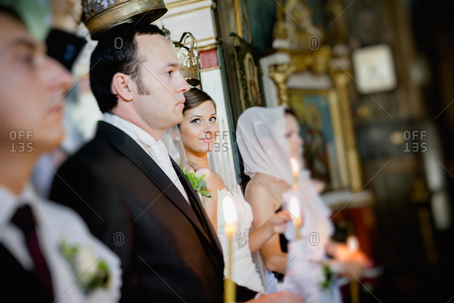 Bride looking at groom during crowning at an Orthodox wedding ceremony