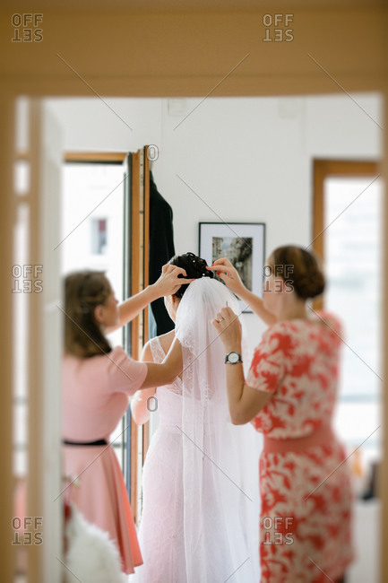 Women fixing the veil of the bride