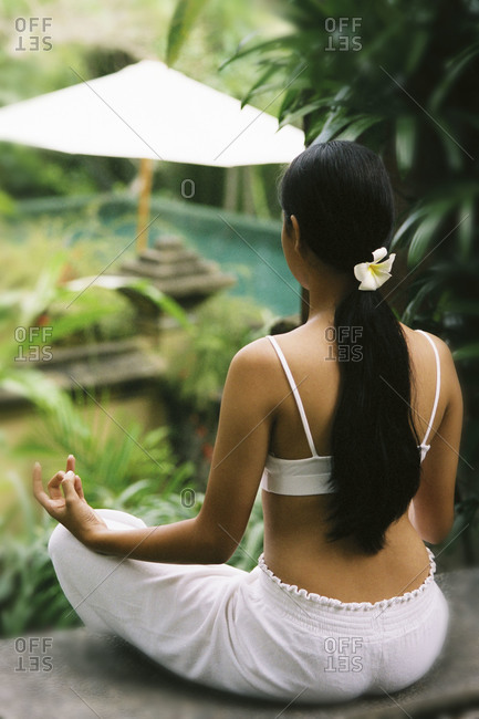 Woman doing yoga in tropical garden