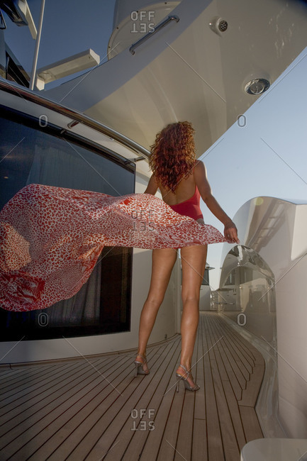 Woman wearing a swimsuit holding a beach wrap standing on a yacht