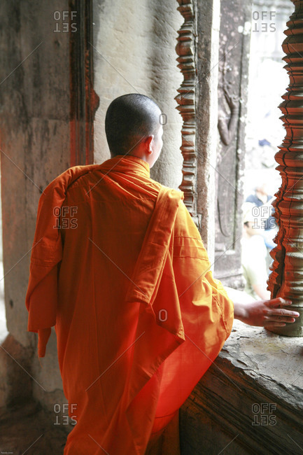 Rear view of a Buddhist monk looking out window