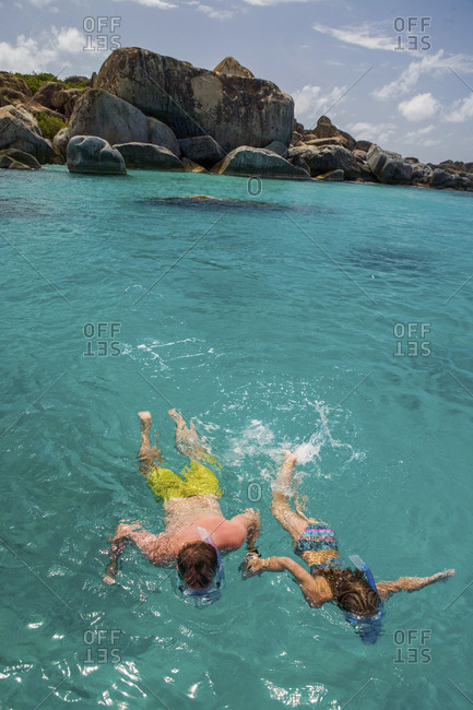 Couple hold hands as they snorkel