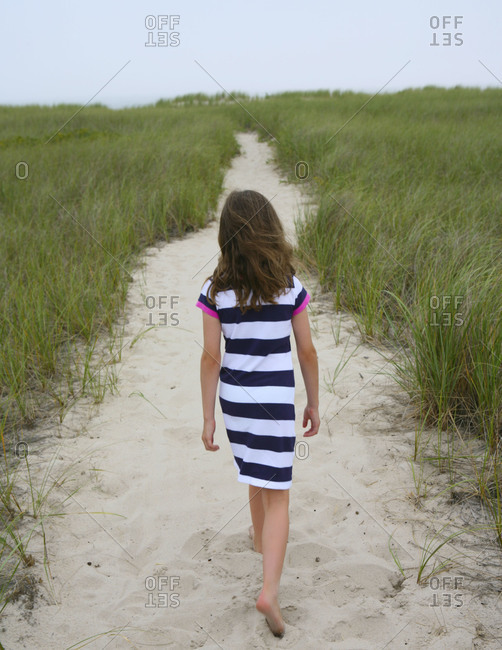 Girl walking on path amid beach grass
