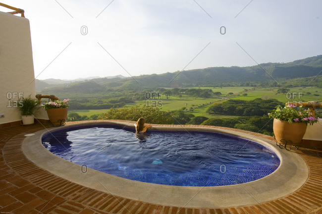 Woman in pool looking out over valley