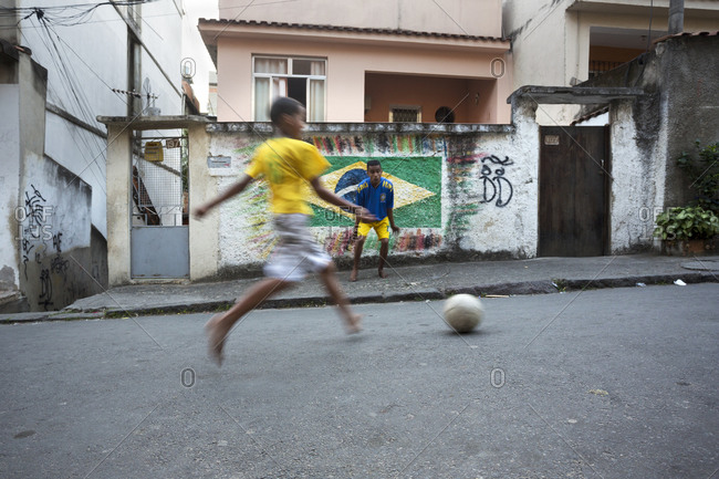 Brazilian children playing football in the streets of Complexo do Alemao favela
