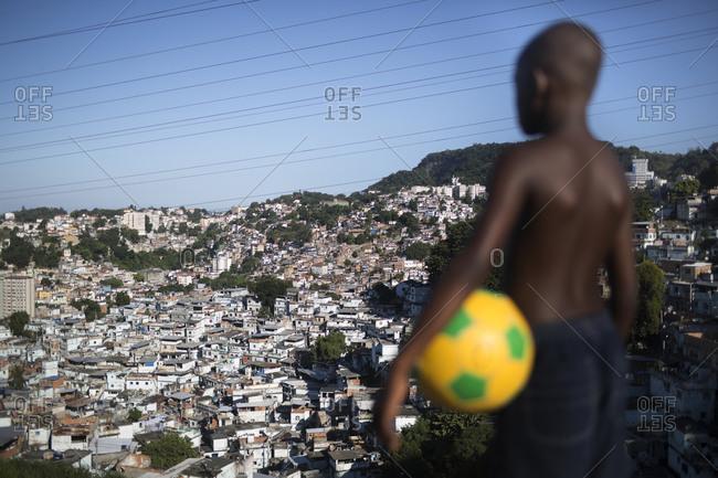 Brazilian boy with a football overlooking Sao Carlos favela, Rio de Janeiro, Brazil