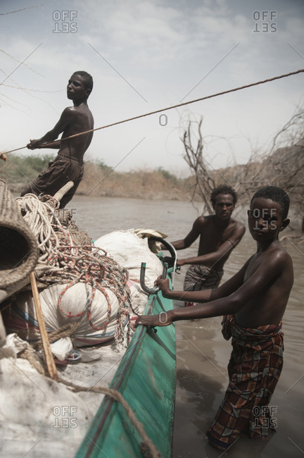 Danakil, Ethiopia - August 20, 2011: Boys move a loaded boat across a river