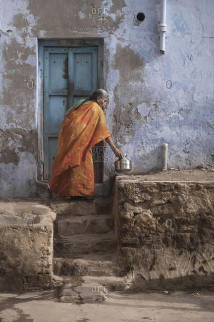Dwarka, India - August 24, 2012: A woman holds a pot of chai