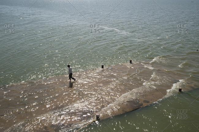 A man on a flooded pier