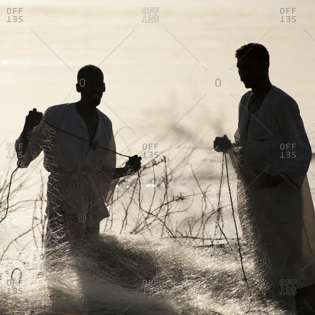 Fishermen sorting nets along the Nile in Karima, Sudan