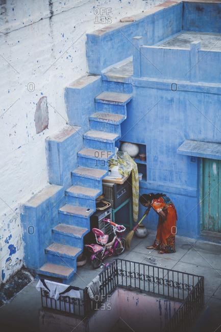 Jodhpur, India - Novemeber, 2013: Woman sweeping the patio