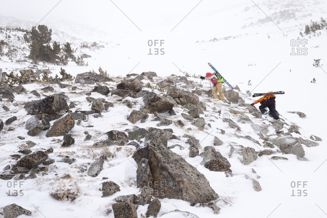 Two female backcountry skiers climbing up a chute during a wind storm in Pony, Montana